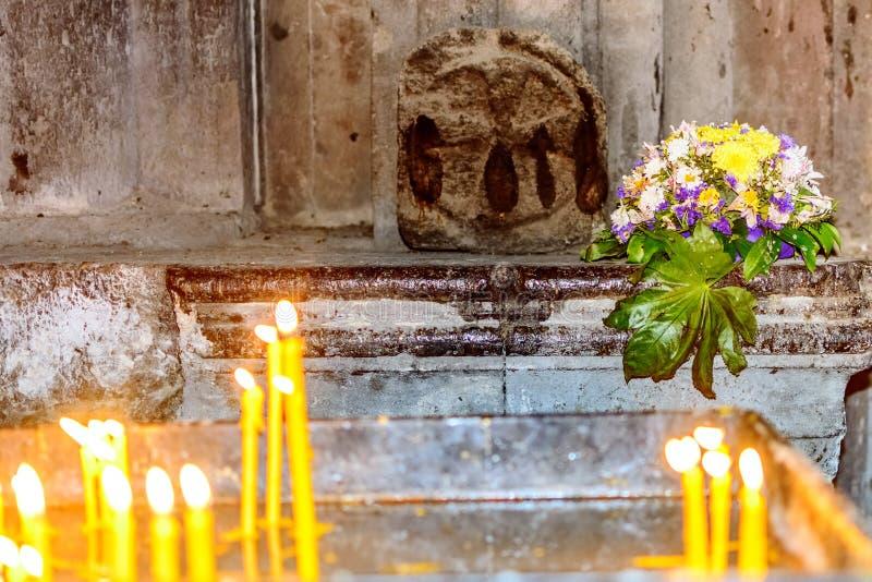 Dois grupos de velas em uma igreja apostólica armênia medieval em primeiro plano em desfocagem e um buquê de flores no fundo fotos de stock royalty free