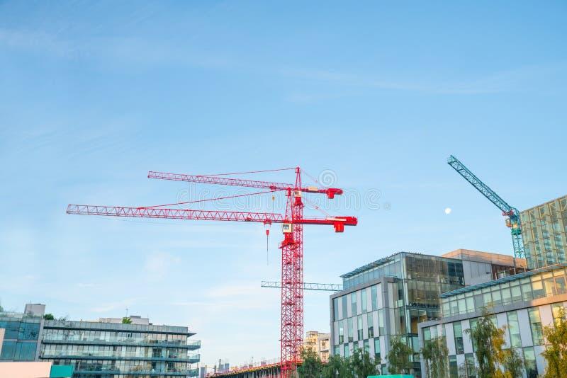 Dois guindastes de construções vermelhos contra o céu azul foto de stock royalty free