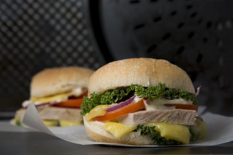 Dois hamburgueres caseiros com carne e queijo grelhados no papel sobre o fundo preto imagens de stock