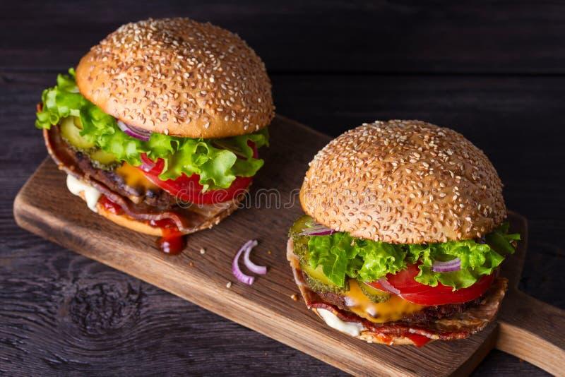 Dois hamburgueres caseiros deliciosos da carne com bacon na placa de desbastamento de madeira foto de stock royalty free