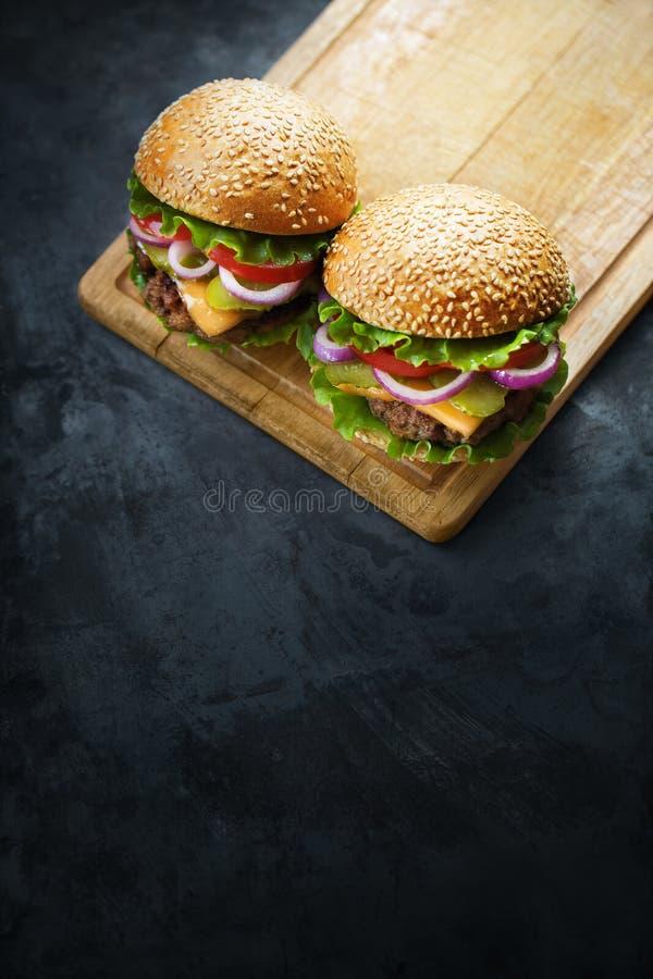 Dois hamburgueres em uma prancha de madeira fotos de stock