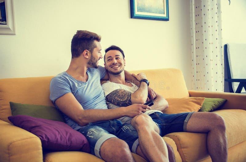 Dois homem gay no sofá que abraçam em casa imagens de stock royalty free