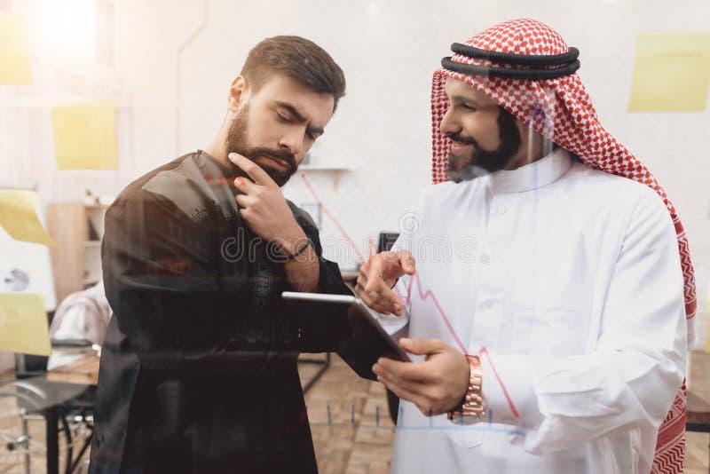 Dois homens árabes que trabalham no escritório Os colegas de trabalho estão tomando notas na frente da placa de vidro fotos de stock