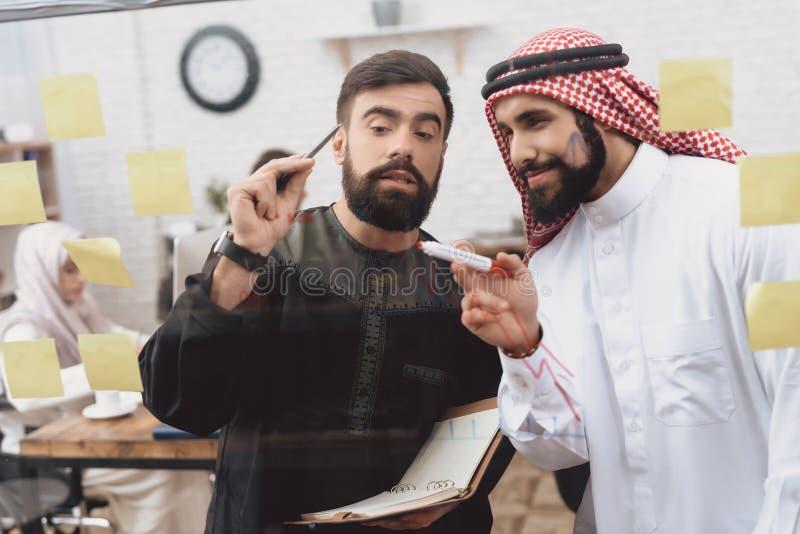 Dois homens árabes que trabalham no escritório Os colegas de trabalho estão tomando notas na placa de vidro imagem de stock royalty free