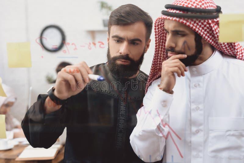 Dois homens árabes que trabalham no escritório Os colegas de trabalho estão tomando notas na placa de vidro fotos de stock royalty free