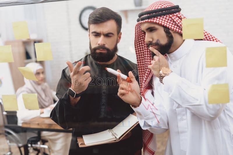 Dois homens árabes que trabalham no escritório Os colegas de trabalho estão tomando notas na placa de vidro fotografia de stock royalty free