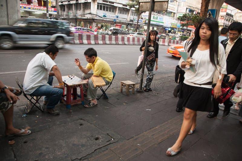 Dois homens apreciam jogar verificadores com os tampões de garrafa que sentam-se em uma rua ruidosa em Banguecoque durante o dia imagem de stock