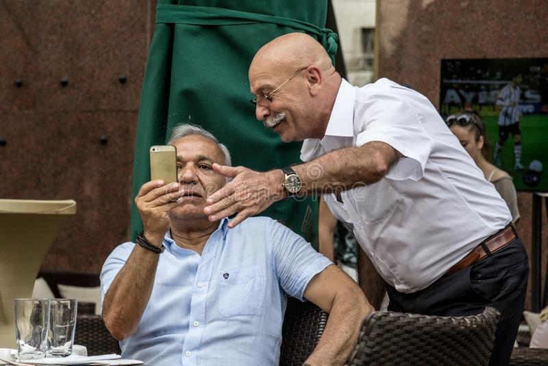 Dois homens brancos do sernior velho que sentam-se em um café que olha um smartphone de Apple IPhone, um que explica os segundos  fotos de stock royalty free