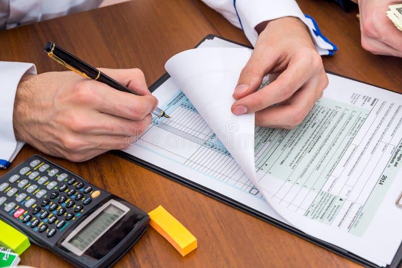 Dois homens calculam o formulário de imposto da renda fotografia de stock