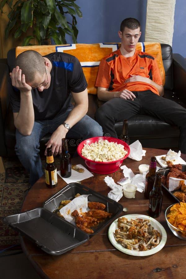 Dois homens cansados após a observação ostentam o jogo na tevê, vertical foto de stock royalty free