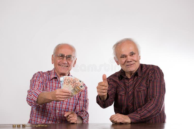 Dois homens com euro- notas s em suas mãos fotografia de stock royalty free