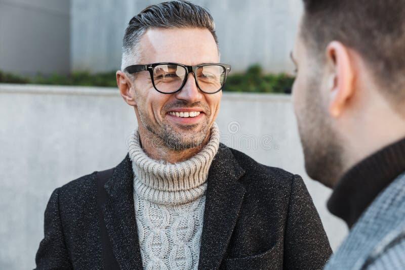 Dois homens consideráveis que vestem o tempo da despesa dos revestimentos foto de stock royalty free