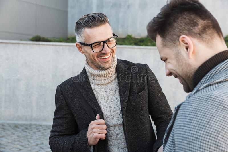 Dois homens consideráveis que vestem o tempo da despesa dos revestimentos fotos de stock royalty free