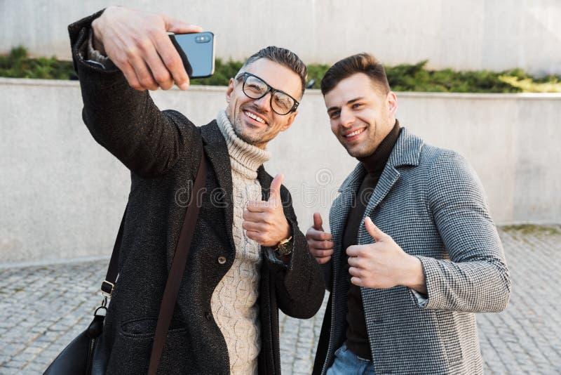 Dois homens consideráveis que vestem o tempo da despesa dos revestimentos imagens de stock