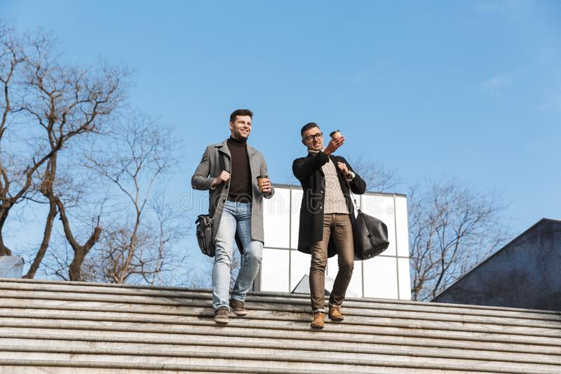 Dois homens consideráveis que vestem o tempo da despesa dos revestimentos fotografia de stock