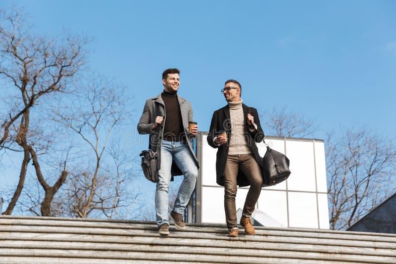 Dois homens consideráveis que vestem o tempo da despesa dos revestimentos imagens de stock royalty free