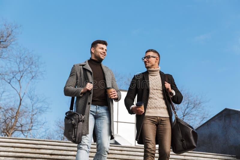 Dois homens consideráveis que vestem o tempo da despesa dos revestimentos foto de stock