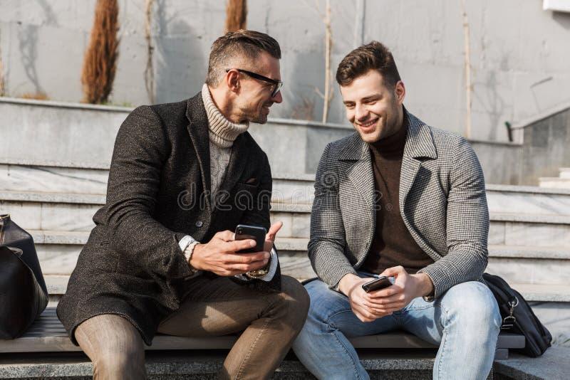 Dois homens consideráveis que vestem o tempo da despesa dos revestimentos imagem de stock royalty free