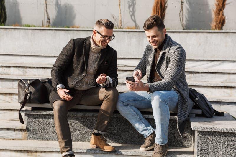 Dois homens consideráveis que vestem o tempo da despesa dos revestimentos fotografia de stock royalty free