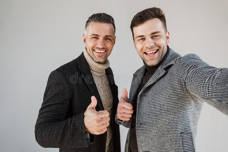 Dois homens consideráveis que vestem revestimentos sobre o fundo cinzento fotografia de stock royalty free
