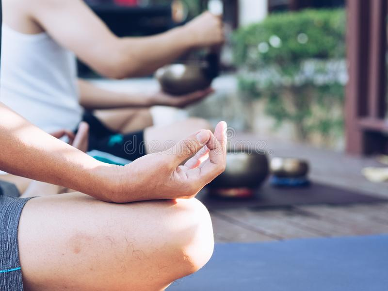 Dois homens da ioga fazem a ioga exterior com bacias do canto imagens de stock