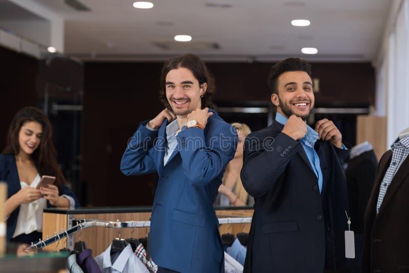 Dois homens de negócio consideráveis que vestem ternos novos ao comprar na loja moderna do Menswear imagem de stock