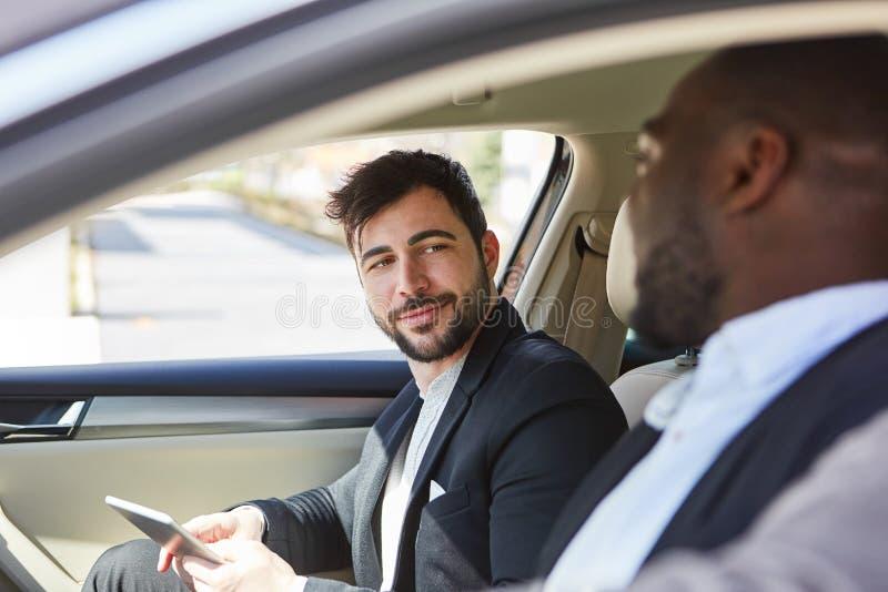 Dois homens de negócio junto no carro fotos de stock