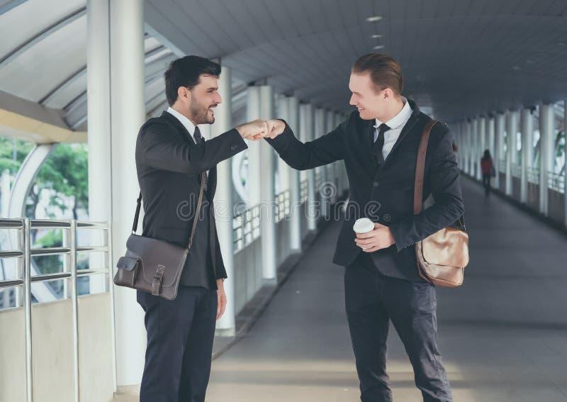 Dois homens de negócio novos consideráveis que dão a colisão do punho e que falam na cidade da maneira da caminhada fotografia de stock royalty free