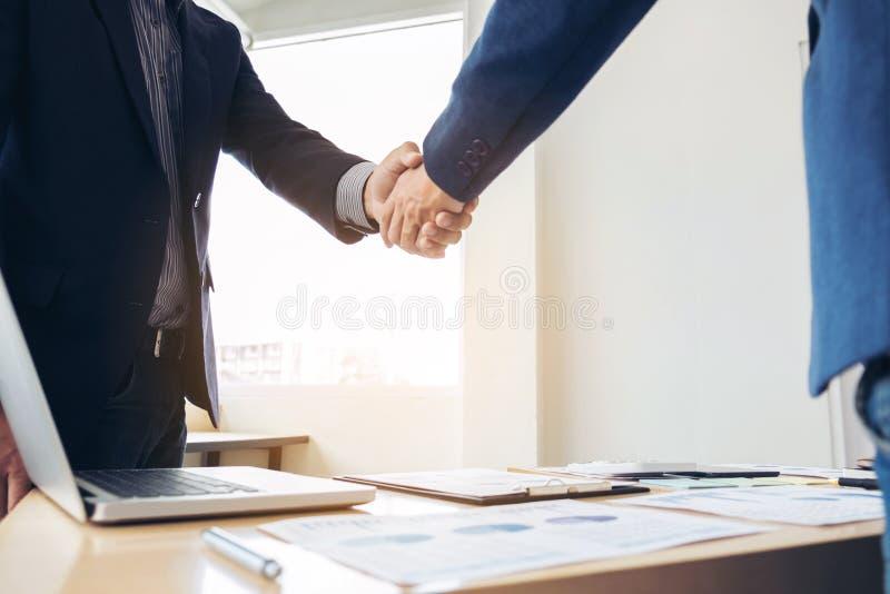 Dois homens de negócio que agitam as mãos durante uma reunião para assinar o acordo e transformar-se um sócio comercial, empresas imagem de stock
