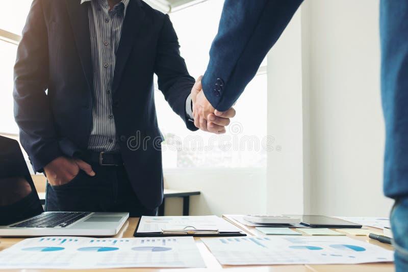 Dois homens de negócio que agitam as mãos durante uma reunião para assinar o acordo e transformar-se um sócio comercial, empresas imagens de stock