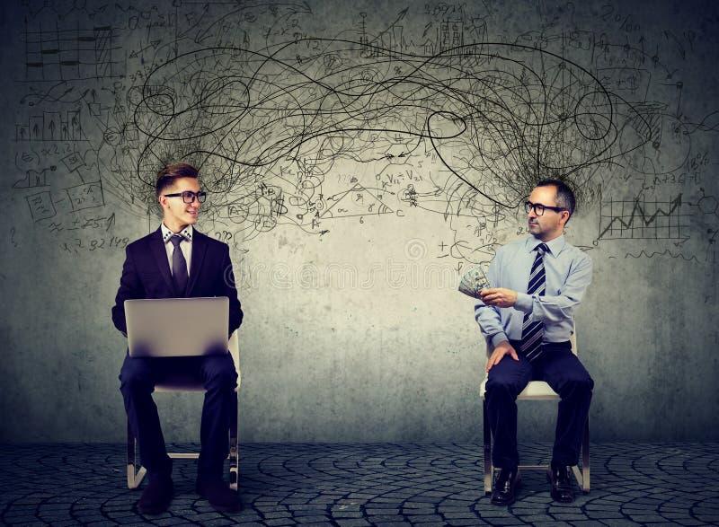 Dois homens de negócio que olham se um com portátil um outro dinheiro de oferecimento para o serviço da TI fotos de stock