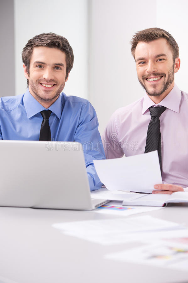 Dois homens de negócio que trabalham junto no portátil no escritório imagem de stock