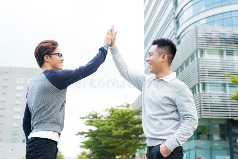 Dois homens de negócios comemoram a vitória, alcance do objetivo, elevação cinco fotografia de stock royalty free