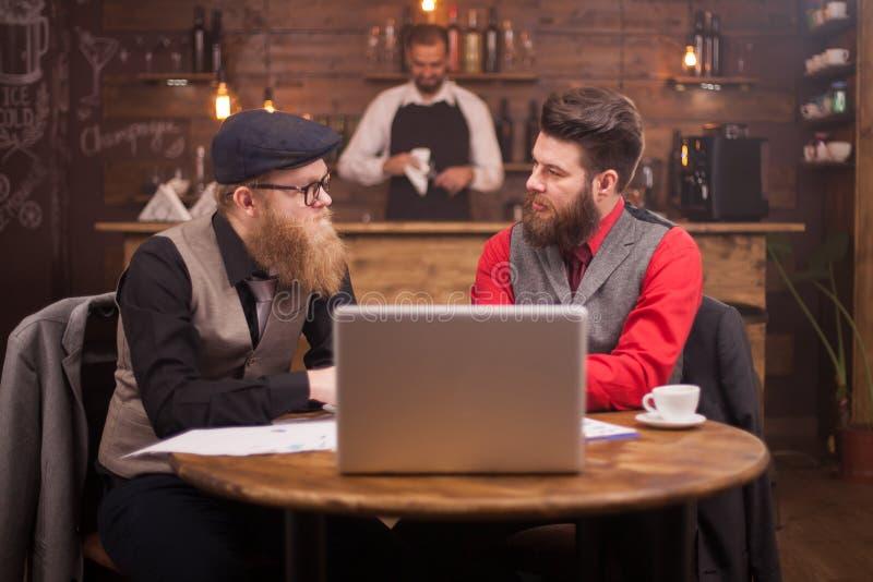 Dois homens de negócios consideráveis que olham se ao falar sobre finanças em um bar do vintage fotografia de stock royalty free
