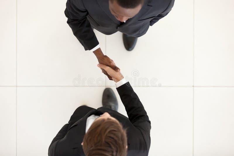 Dois homens de negócios diversos agitam as mãos que estão no escritório, vista superior imagens de stock royalty free
