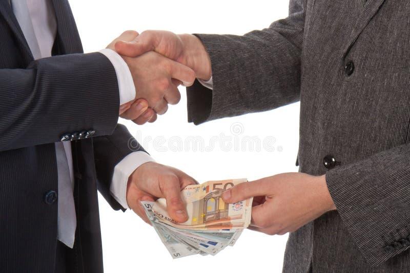 Dois homens de negócios e dinheiros pagar fotos de stock