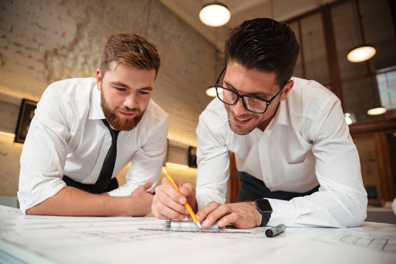 Dois homens de negócios entusiasmado novos que trabalham em um plano de negócios fotos de stock royalty free