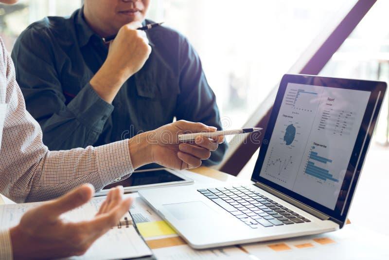 Dois homens de negócios estão analisando junto o gráfico dos dados financeiros e estão apontando à tela de laptop fotos de stock
