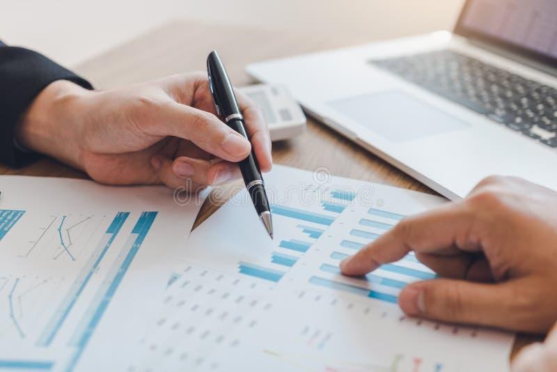 Dois homens de negócios estão apontando ao gráfico de custo da empresa e estão analisando então junto fotografia de stock royalty free