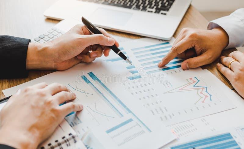 Dois homens de negócios estão apontando ao papel de gráfico das vendas da empresa e estão analisando então junto imagens de stock royalty free
