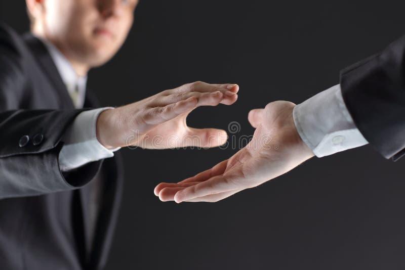 Dois homens de negócios estão guardando para fora suas mãos para um aperto de mão imagens de stock royalty free