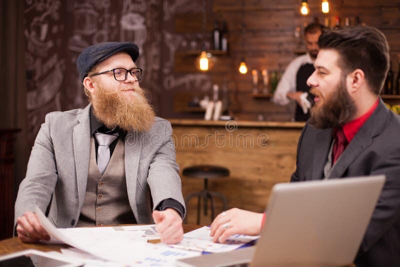 Dois homens de negócios farpados consideráveis que alcançam a um acordo durante sua reunião em uma cafetaria fotografia de stock royalty free