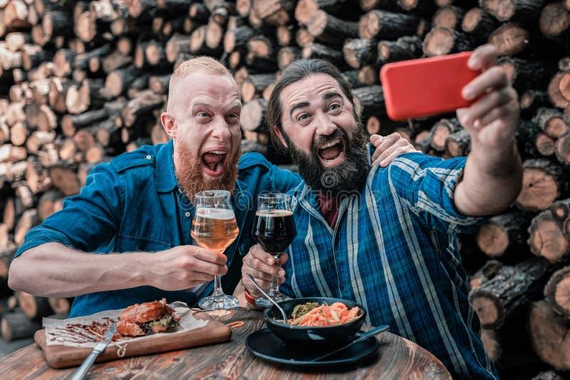 Dois homens de negócios maduros que fazem a foto que senta-se junto no bar imagens de stock royalty free