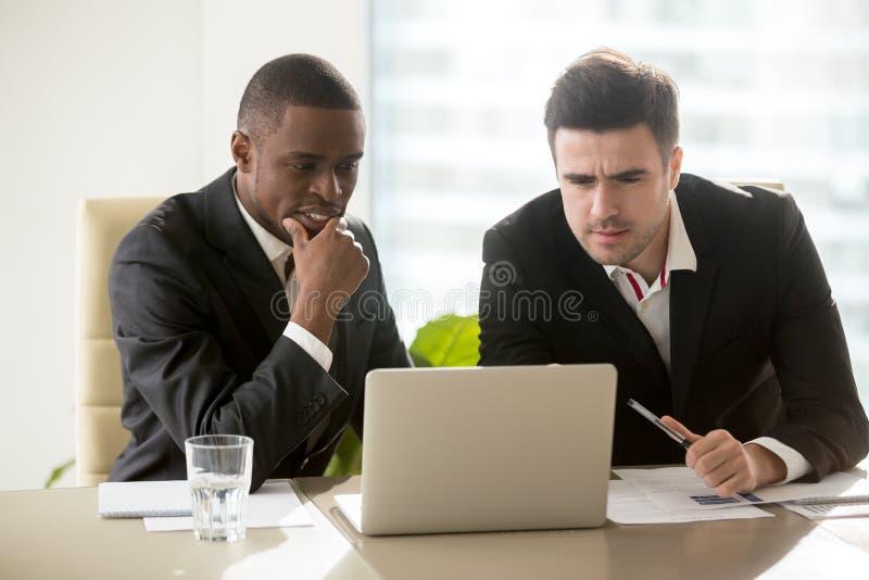Dois homens de negócios na reunião que olha a tela do portátil, pensativa foto de stock