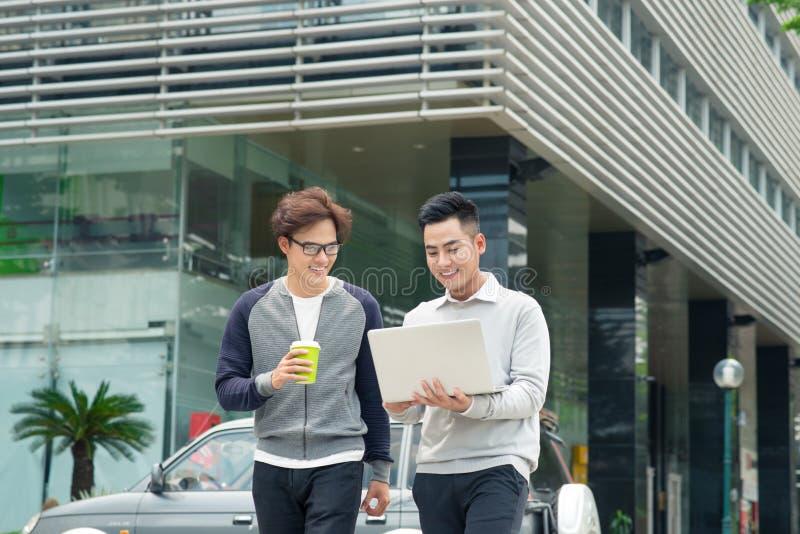 Dois homens de negócios novos de sorriso que andam e que falam na cidade foto de stock royalty free