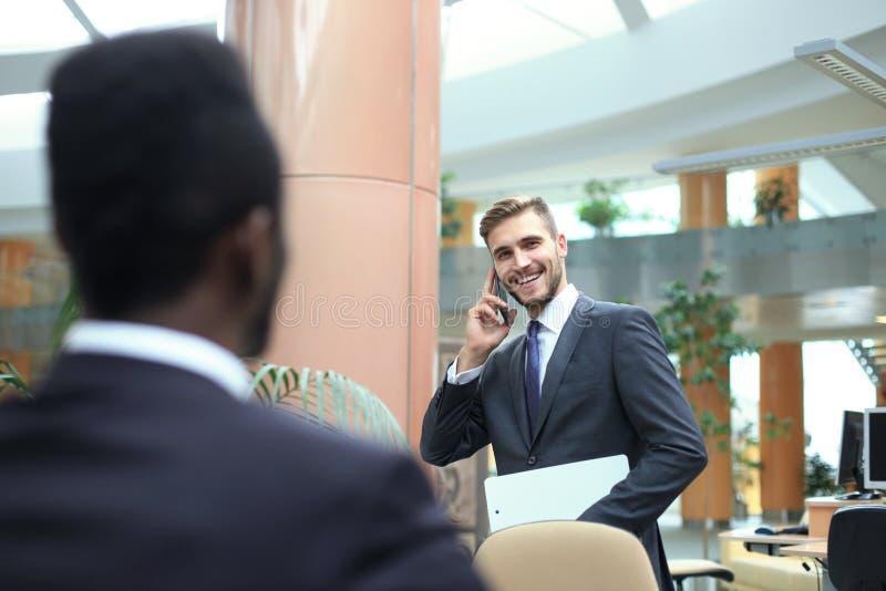 Dois homens de negócios novos multinacionais no terno que comunicam-se no telefone celular imagem de stock royalty free