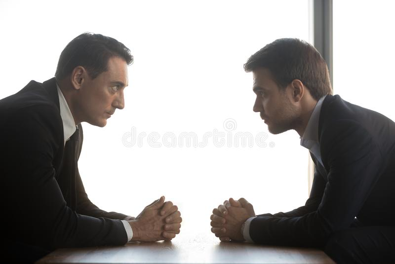 Dois homens de negócios olham se oposto de assento, conceito da rivalidade foto de stock