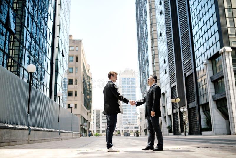 Dois homens de negócios que agitam as mãos em construções incorporadas do escritório do fundo fotografia de stock