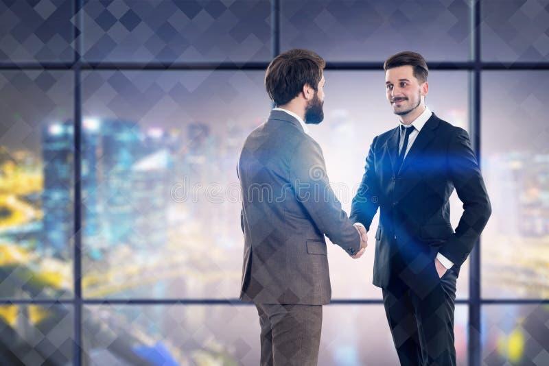 Dois homens de negócios que agitam as mãos no escritório da noite fotografia de stock