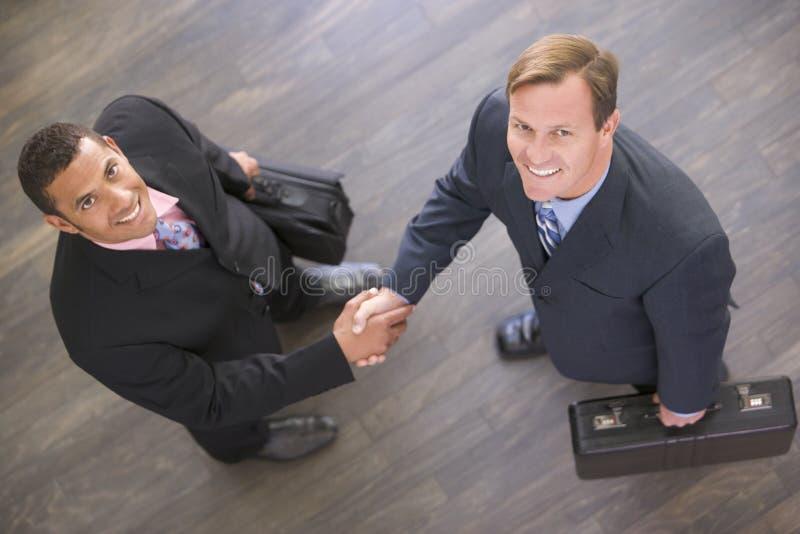 Dois homens de negócios que agitam dentro o sorriso das mãos foto de stock royalty free
